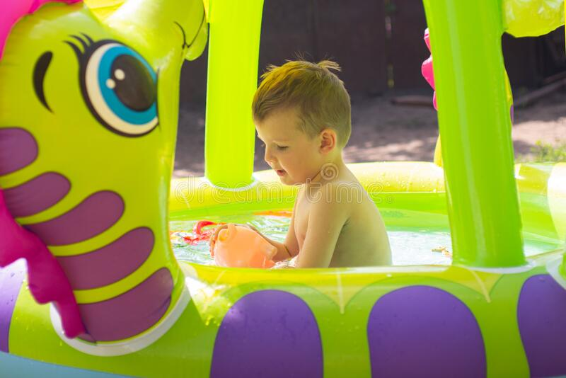 Children playing and active leisure - swimming pool concept. Child having fun in summertime. Little child boy having fun in the royalty free stock photos