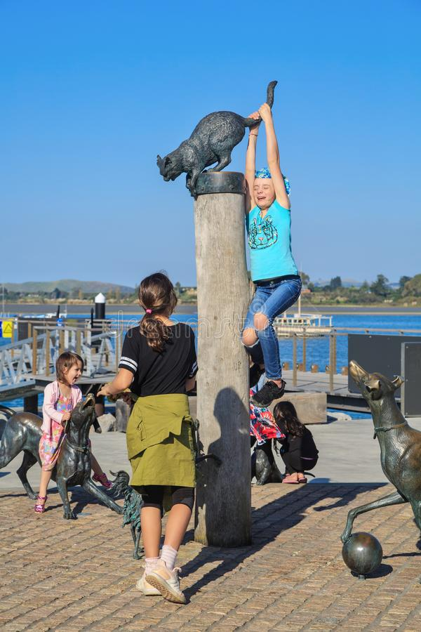 Children playing on animal sculptures, Tauranga, New Zealand. Children climbing on the `Hairy Maclary` sculptures in Tauranga`s waterfront park. Hairy Maclary, a stock photo