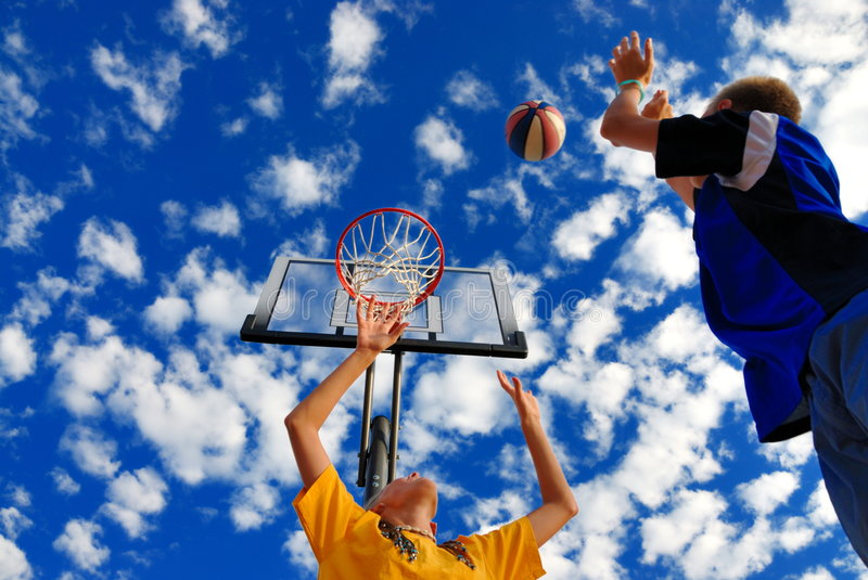 Children playing basketball. With deep blue cloudy sky stock photos