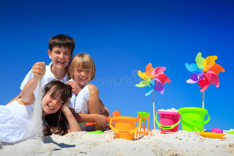 Children playing on beach. Children playing in sand at a beach with colorful sand pails and pinwheels. Beautiful blue sky background royalty free stock images