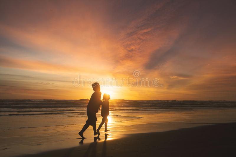Children playing on the beach at sunset time stock photo