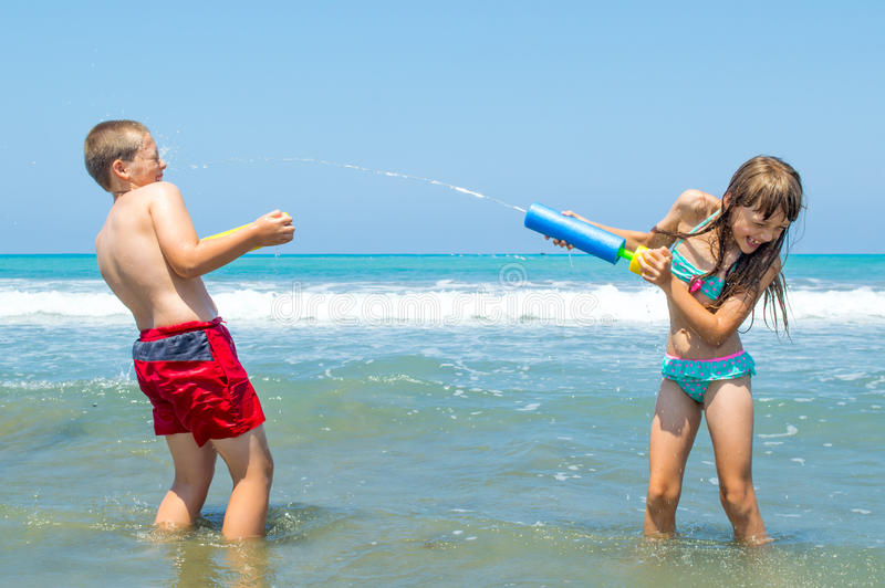 Children playing on the beach waterfighting. Small children fighting each other with water guns whilst playing on the beach stock image