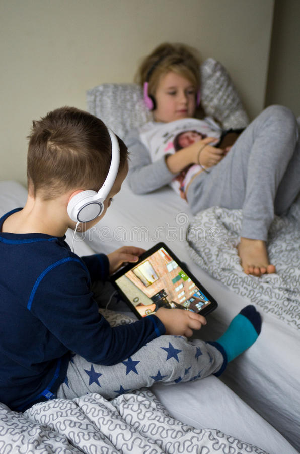 Children playing in bed with their tablets and phones. Two children playing in large bedroom bed next to big window, using their mobile devices such as phones royalty free stock photography