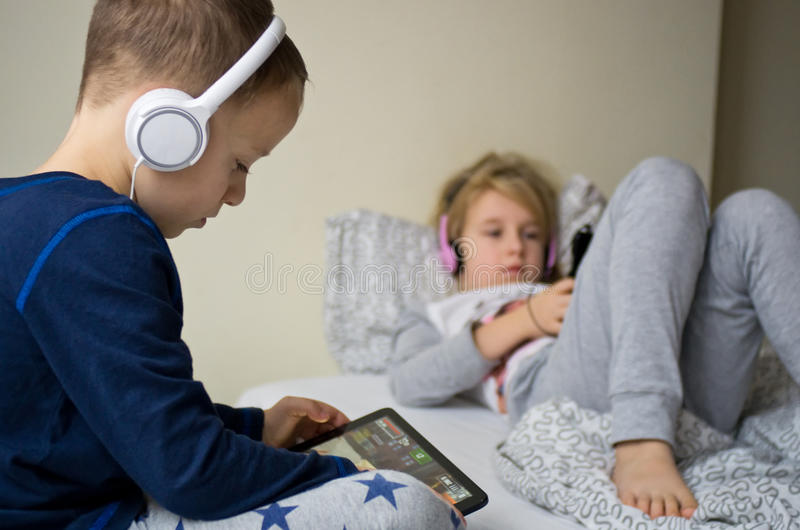 Children playing in bed with their tablets and phones. Two children playing in large bedroom bed next to big window, using their mobile devices such as phones royalty free stock images