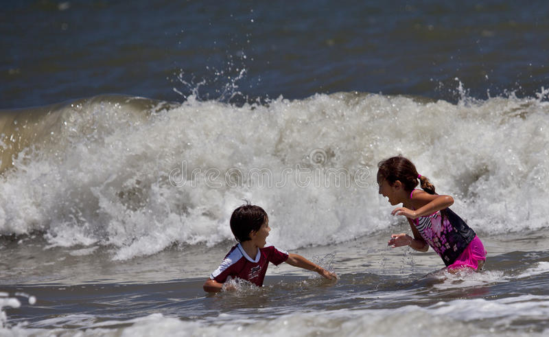 Children Playing in the Big Surf. Two children, a boy and a girl, playing in the surf reacting to a large incoming wave and preparing to get away royalty free stock image
