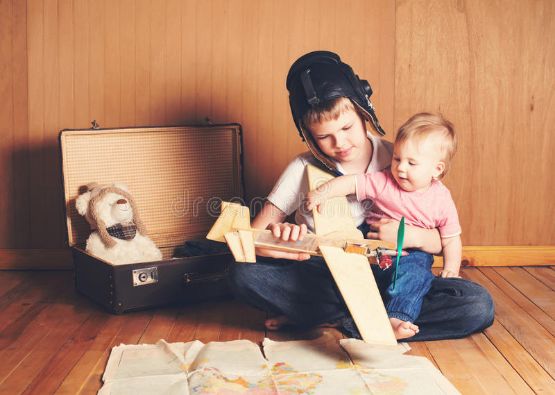 Children playing. Boy in pilot helmet with plane model and suitcase, dreaming of adventure. Journey. Brother holding his little b stock photo