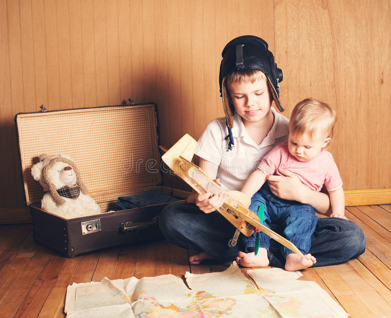 Children playing. Boy in pilot helmet with plane model and suitcase, dreaming of adventure. Journey. Brother holding his little b stock image