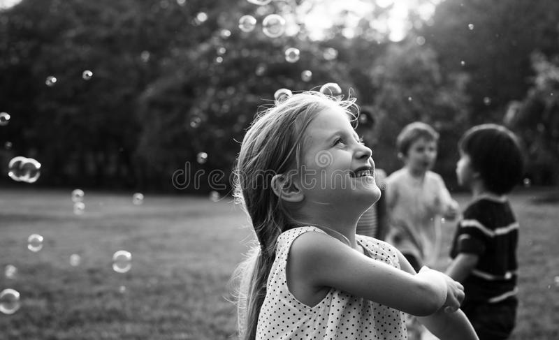 Children is playing bubbles in a park stock photos