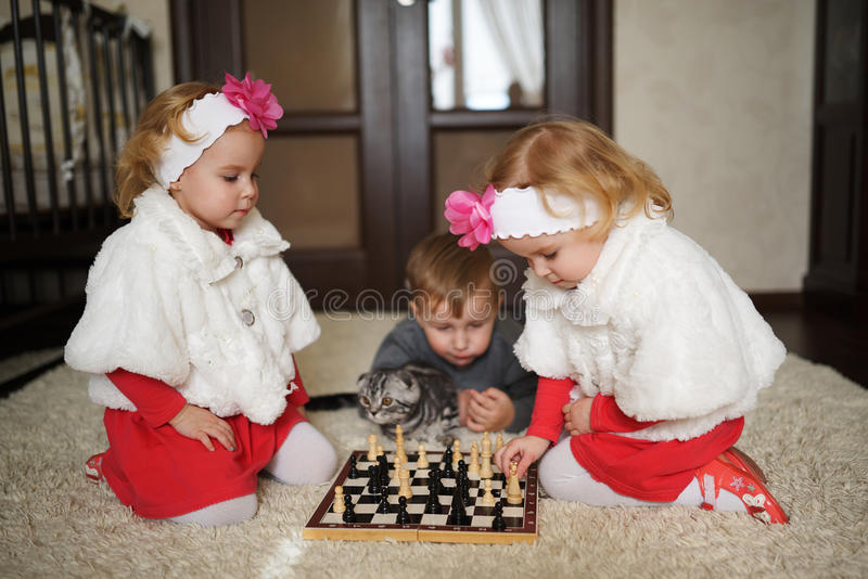 Children playing chess lying on floor royalty free stock photography