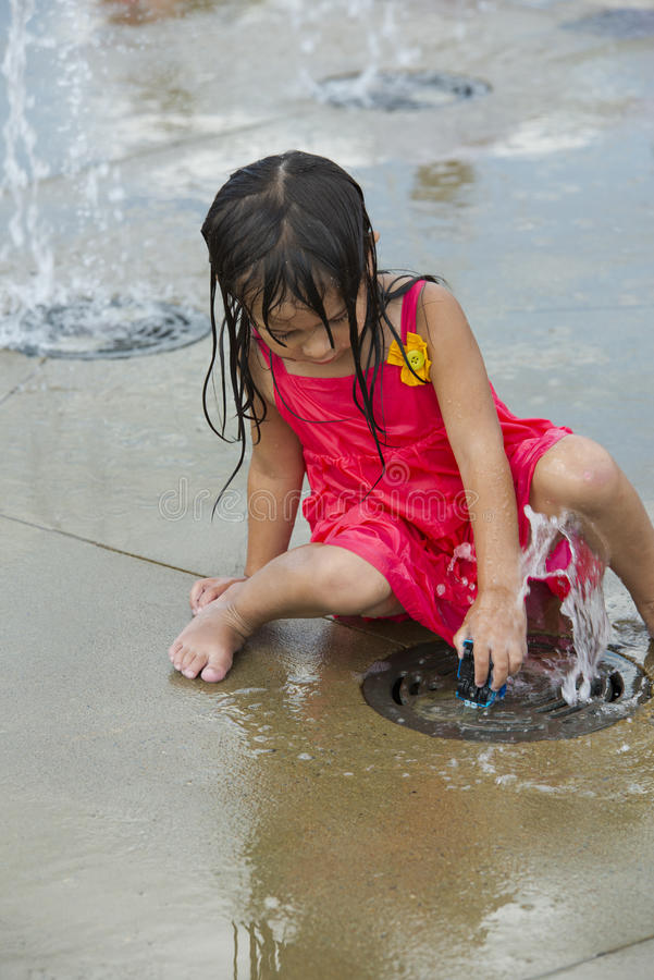 Children playing in a city water park play ground royalty free stock photography