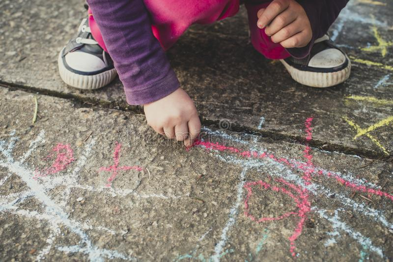 Children playing with colored chalks stock photography
