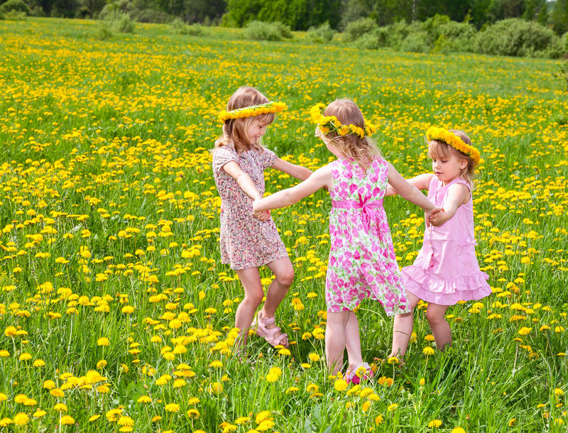 Children playing on a dandelion field royalty free stock photos