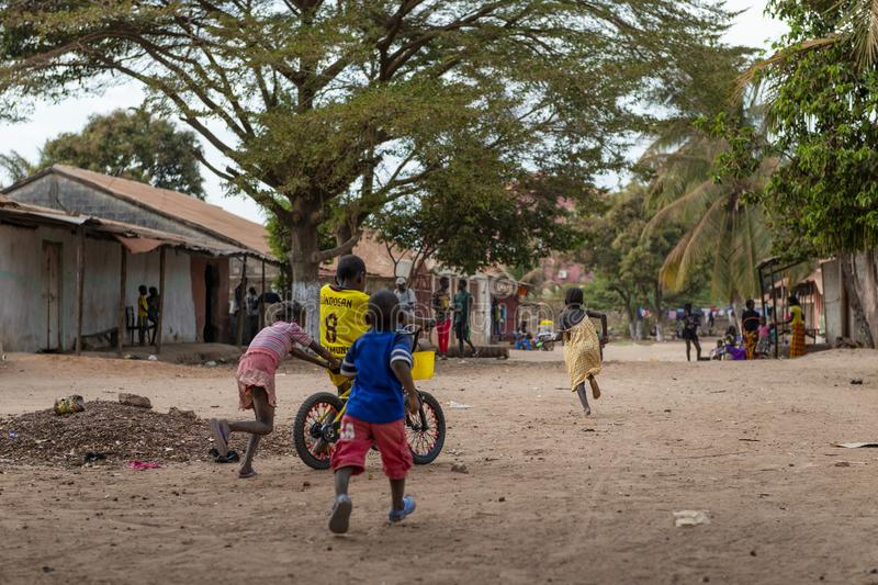Children playing at a dirt street in the city of Bissau, in Guinea-Bissau. Bissau, Republic of Guinea-Bissau - February 8, 2018: Children playing at a dirt royalty free stock photography