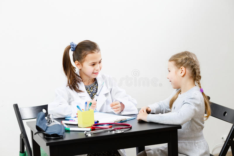 Children playing doctor and patient stock image