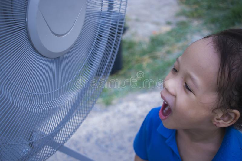 A children playing electric fan and enjoying cool wind in summer season royalty free stock photo