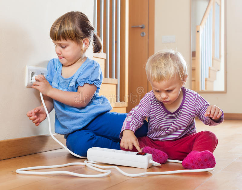 Children playing with electrical extension and outlet stock photography
