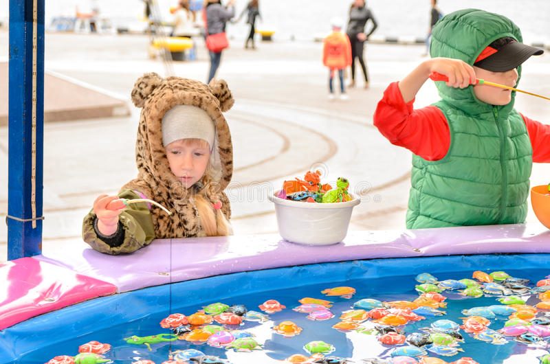 Children playing at fishing pond game at fun fair stock for Fish pond game