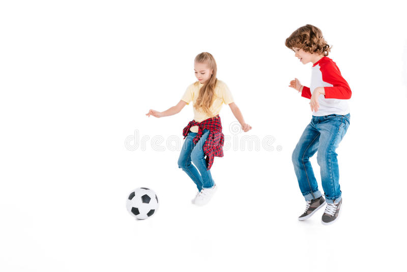 Children playing football. Boy and girl playing football isolated on white, children sport concept royalty free stock image