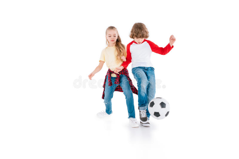 Children playing football. Boy and girl playing football isolated on white, children sport concept stock image