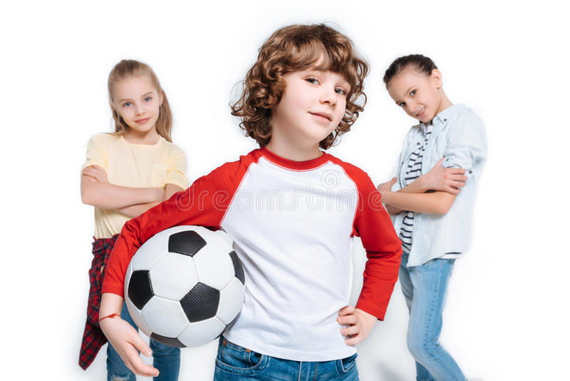 Children playing football. Group of friends posing with soccer ball isolated on white, children sport concept royalty free stock images