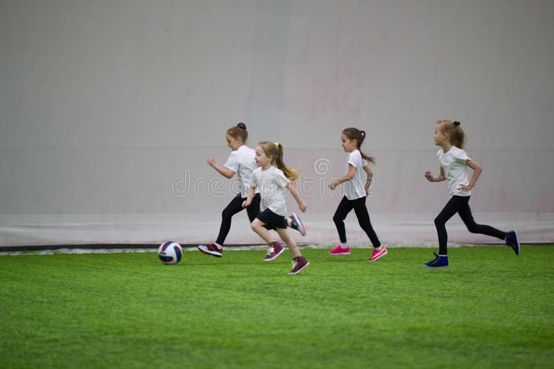 Children playing football indoors. An excited little girls following the ball stock photos