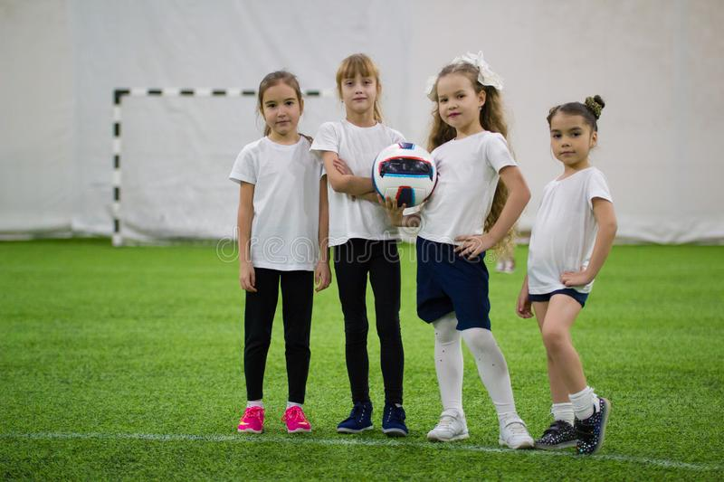 Children playing football indoors. Football team contains four girls stock photos