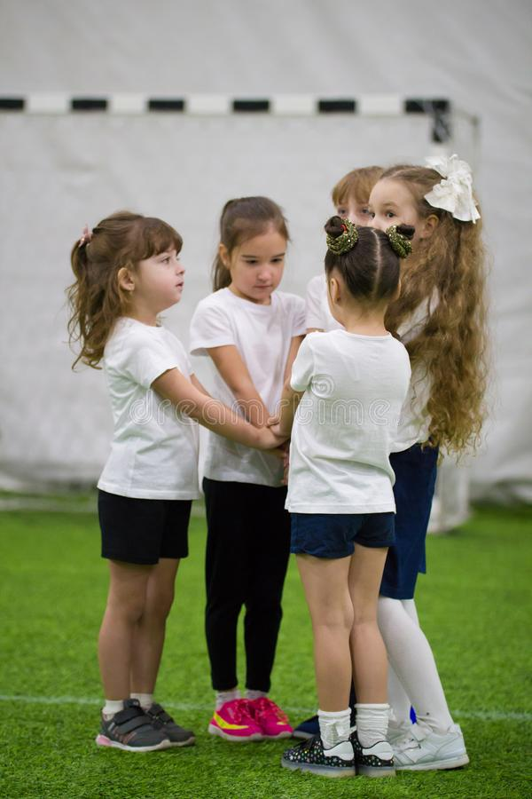 Children playing football indoors. Kids doing a team support. Team gesture royalty free stock photo