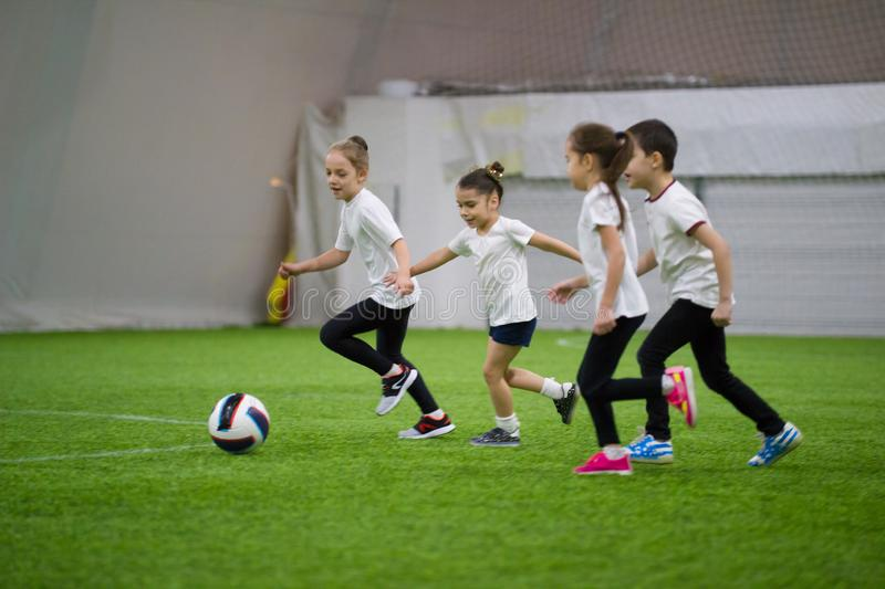 Children playing football indoors. Kids running on the field after the ball stock images