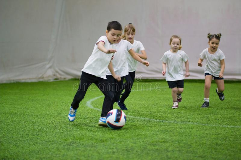 Children playing football indoors. Kids running on the field. A little boy leading the ball stock images