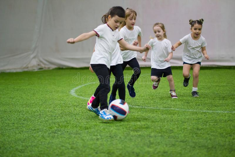 Children playing football indoors. Kids running on the field. A little boy is ready to kick the ball royalty free stock photography