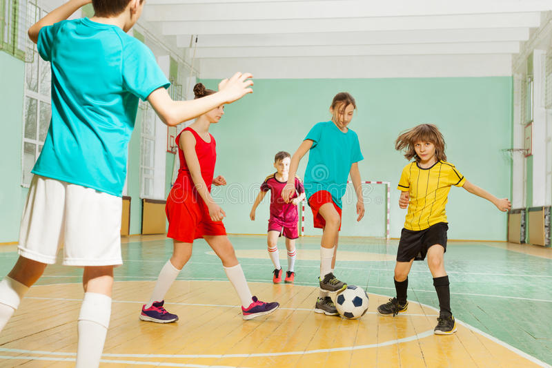 Children playing football in school sports hall royalty free stock images