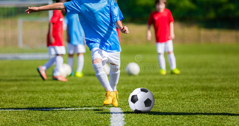 Children playing football soccer game on sports field. Young boy kicking football soccer ball stock photo