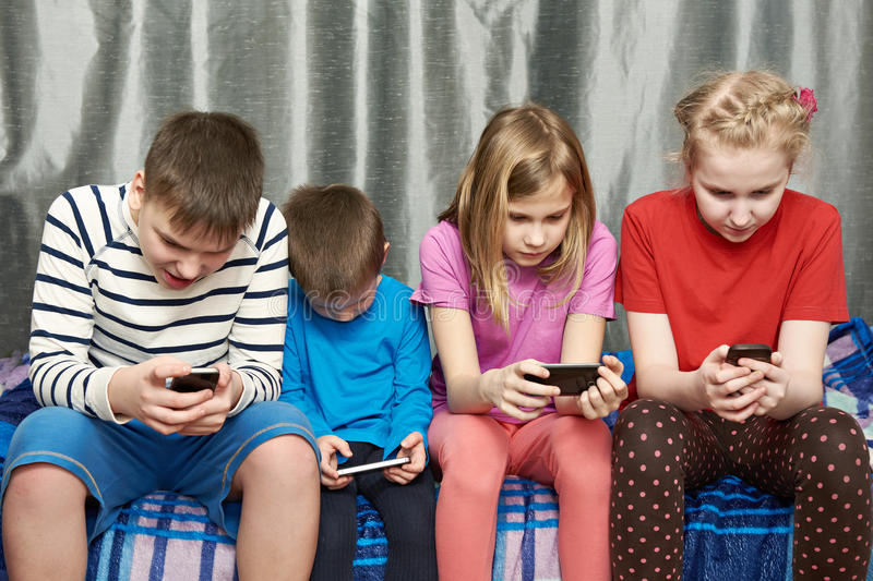 Children playing game on mobile phones stock photo