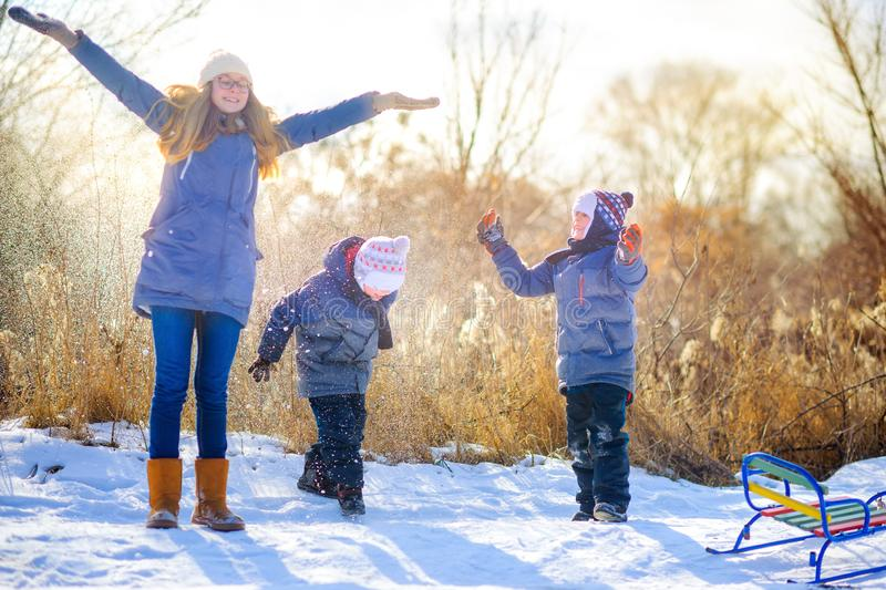 Children playing and having fun in the winter forest. At sunset stock photos