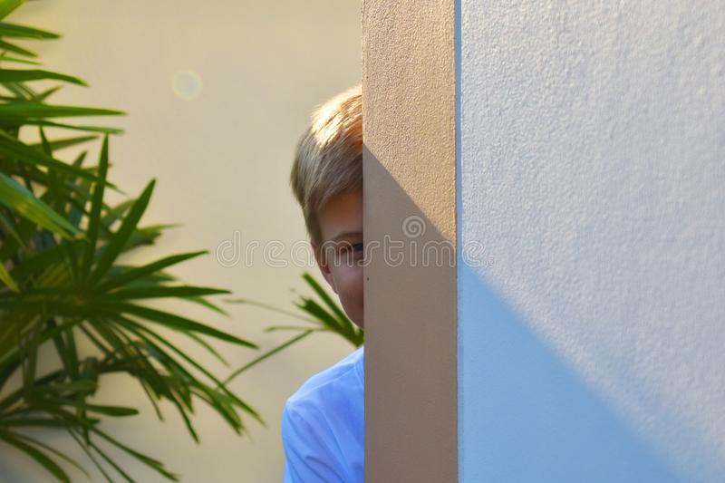 A boy looks out from behind the house. The child slyly peeping. Hide-and-seek. royalty free stock photo