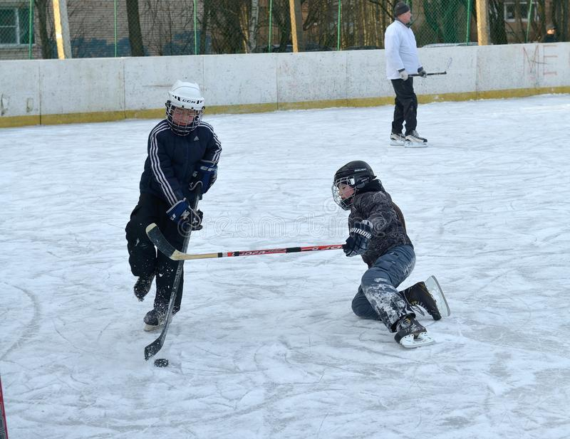 Children playing hockey on the rink. The game of hockey in the winter on the outdoor rink. The Town Of Sosnovy Bor. Russia. January 2015 stock photo