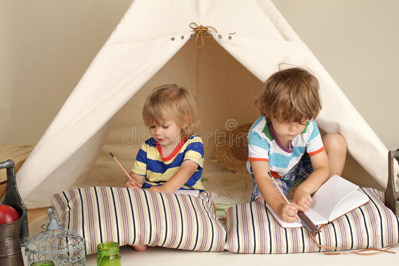 Children playing at home indoors with a teepee tent stock image