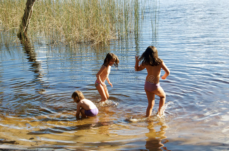 Children playing in lake royalty free stock images