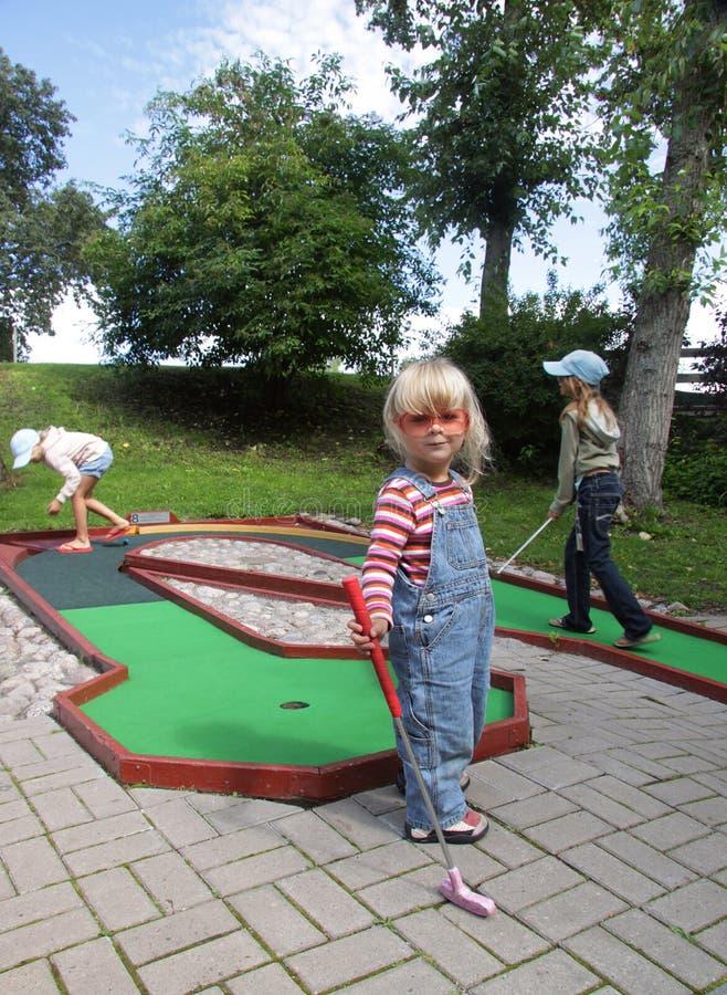 Children playing mini golf stock image