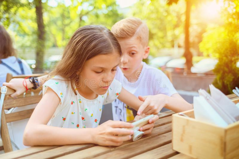 Children playing with mobile phone at terrace - Portrait of positive kids having fun together with smart phone. – happy boy and girl addicted to modern royalty free stock images