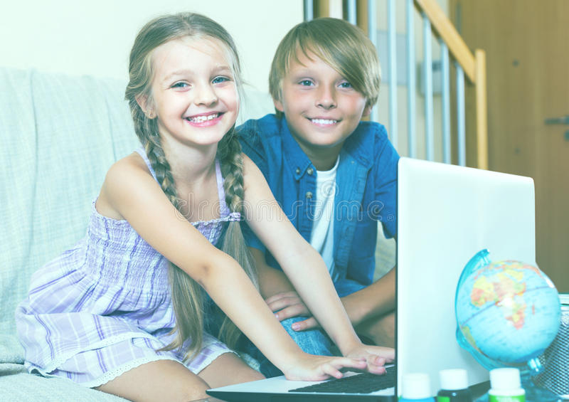 Children playing online game. Portrait of happy smiling children busy with game on laptop royalty free stock photos