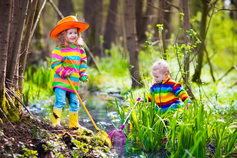Children playing outdoors catching frog royalty free stock photos
