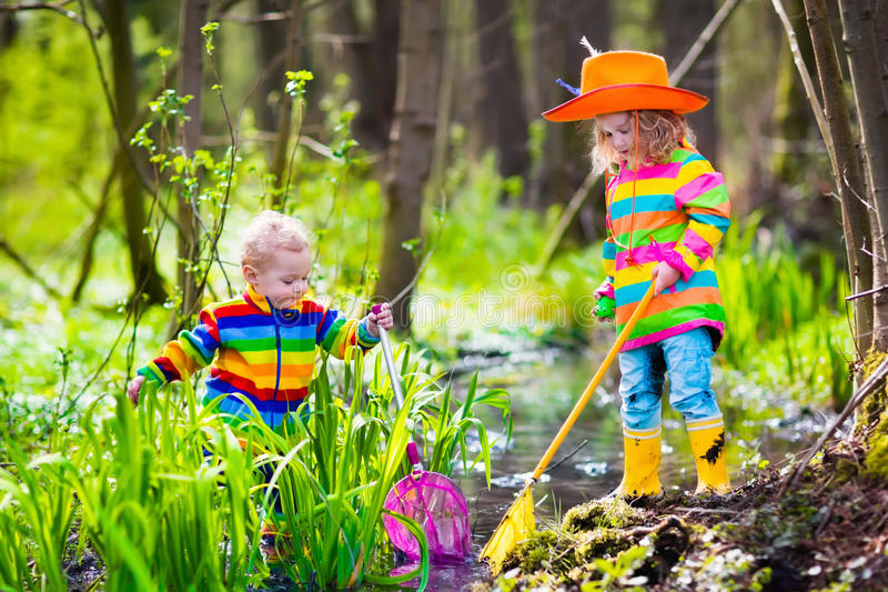 Children playing outdoors catching frog royalty free stock images