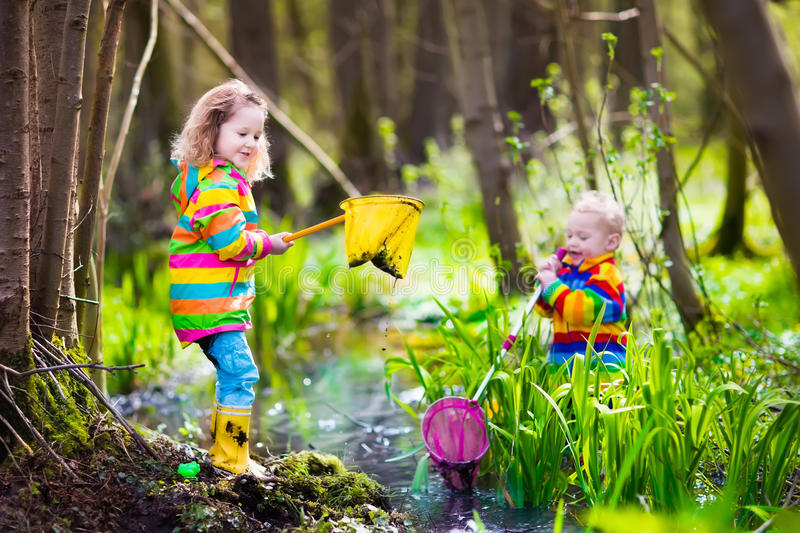 Children playing outdoors catching frog royalty free stock image