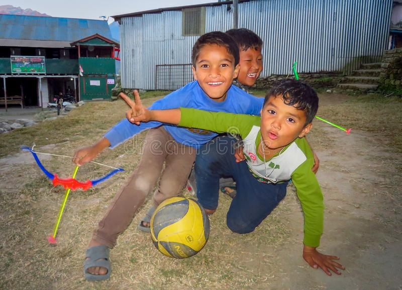 Children playing outside in the small mountain village Num, Nepal. Num, Sankhuwasabha District, Nepal - 11/17/2017 : Boys playing outside soccer and bow and stock photography