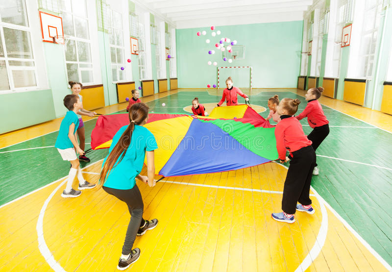 Children playing parachute games in sports hall stock images