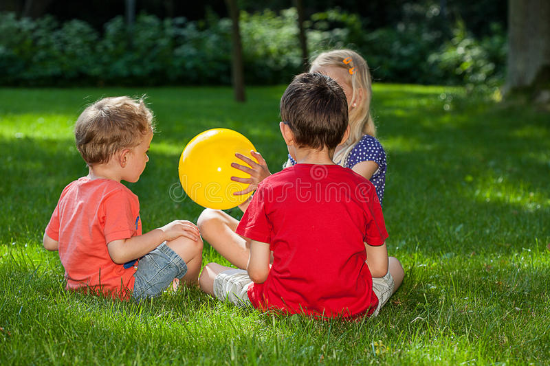 Children playing in the park. Three children playing with a yellow ball on the grass stock photos