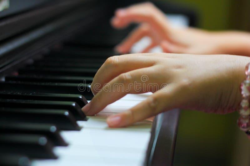 Children hand on piano key stock photo