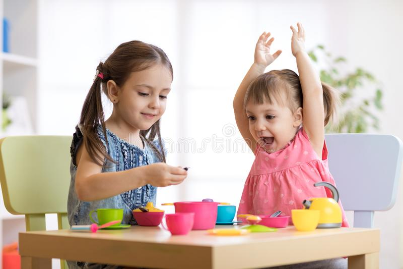 Children playing with plastic tableware royalty free stock photo