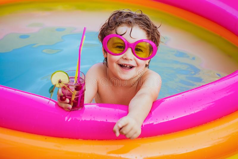 Children playing in pool. Child water toys. Stylish sunglasses. Beach Clubs in Ibiza. Beach party. Child swimming pool. Kids Swimming Pool Concept. Child water royalty free stock photos